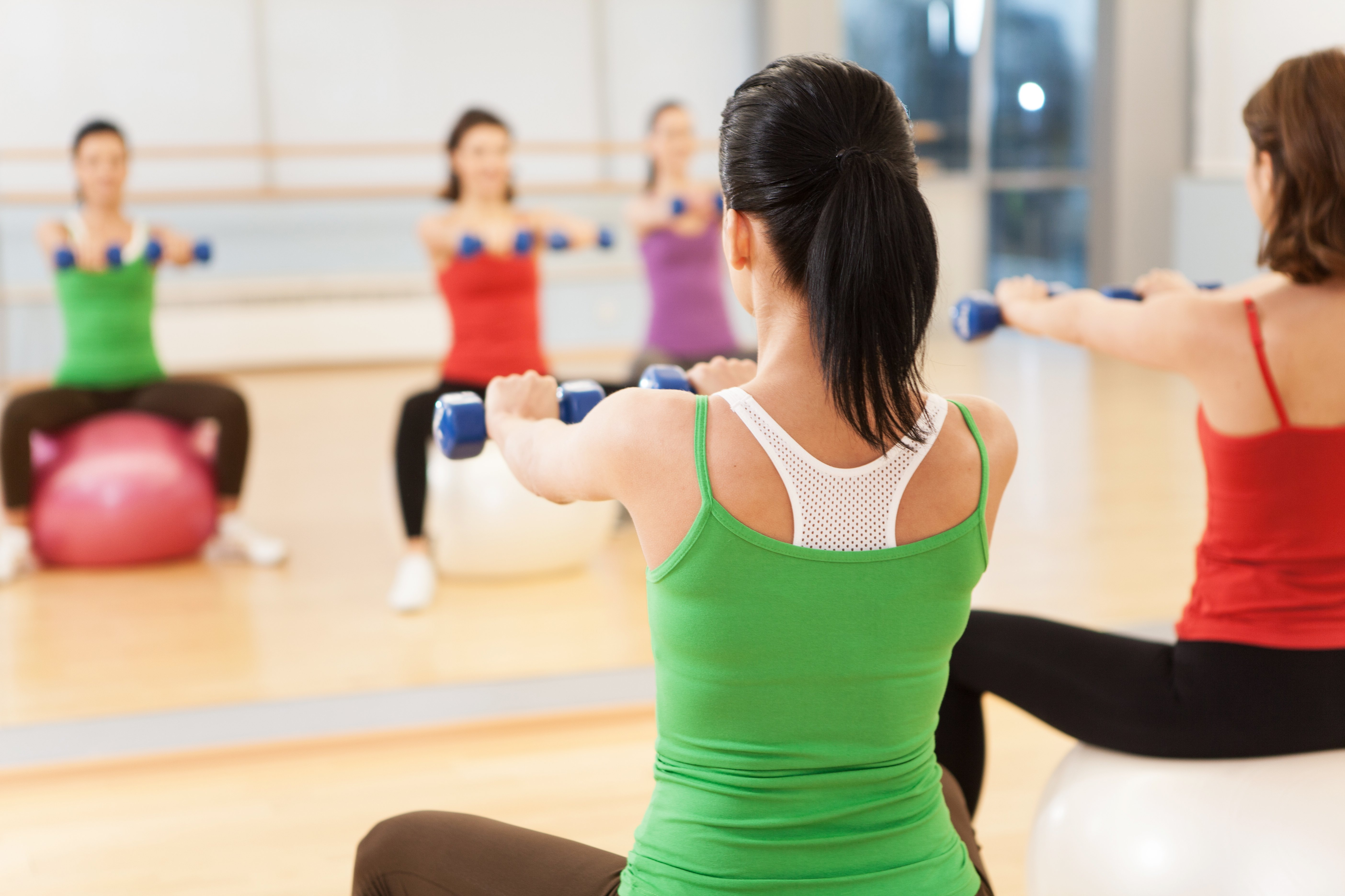 big man in the woodspilates aerobics women group with stability ball
