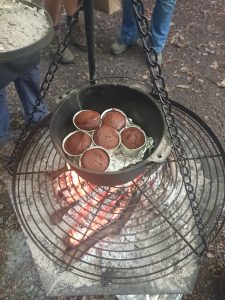 Cakes being cooked in a Dutch oven